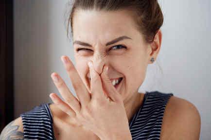 Mujer tapándose la nariz divertida