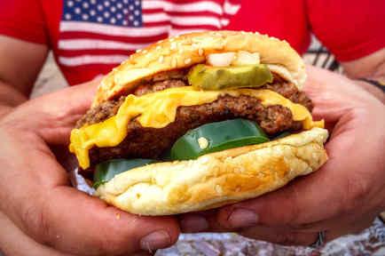 Hombre sosteniendo una hamburguesa en las manos