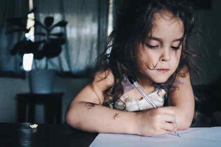 Niña pequeña escribiendo una carta