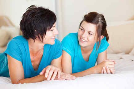 Madre e hija hablando en la cama