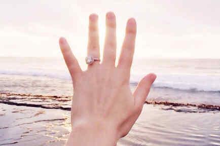 Mujer mostrando su anillo de compromiso en la playa