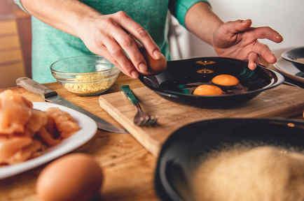 Mujer cocina huevos y pollo
