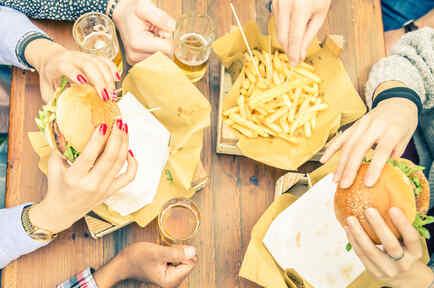 Mujeres comiendo hamburguesas con patatas fritas