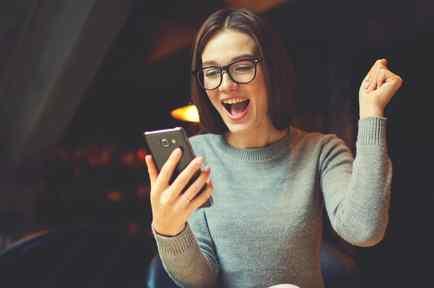 Mujer joven mirando el teléfono móvil y festejando