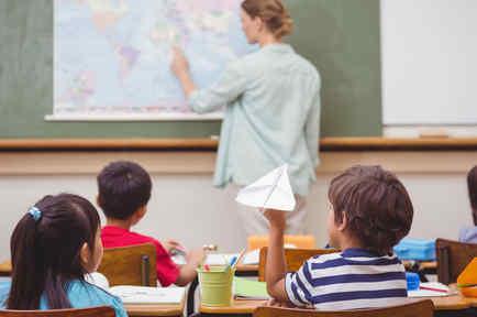 Niño arrojando un avión de papel en clase