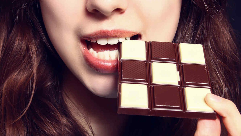 Mujer comiendo chocolate blanco y negro