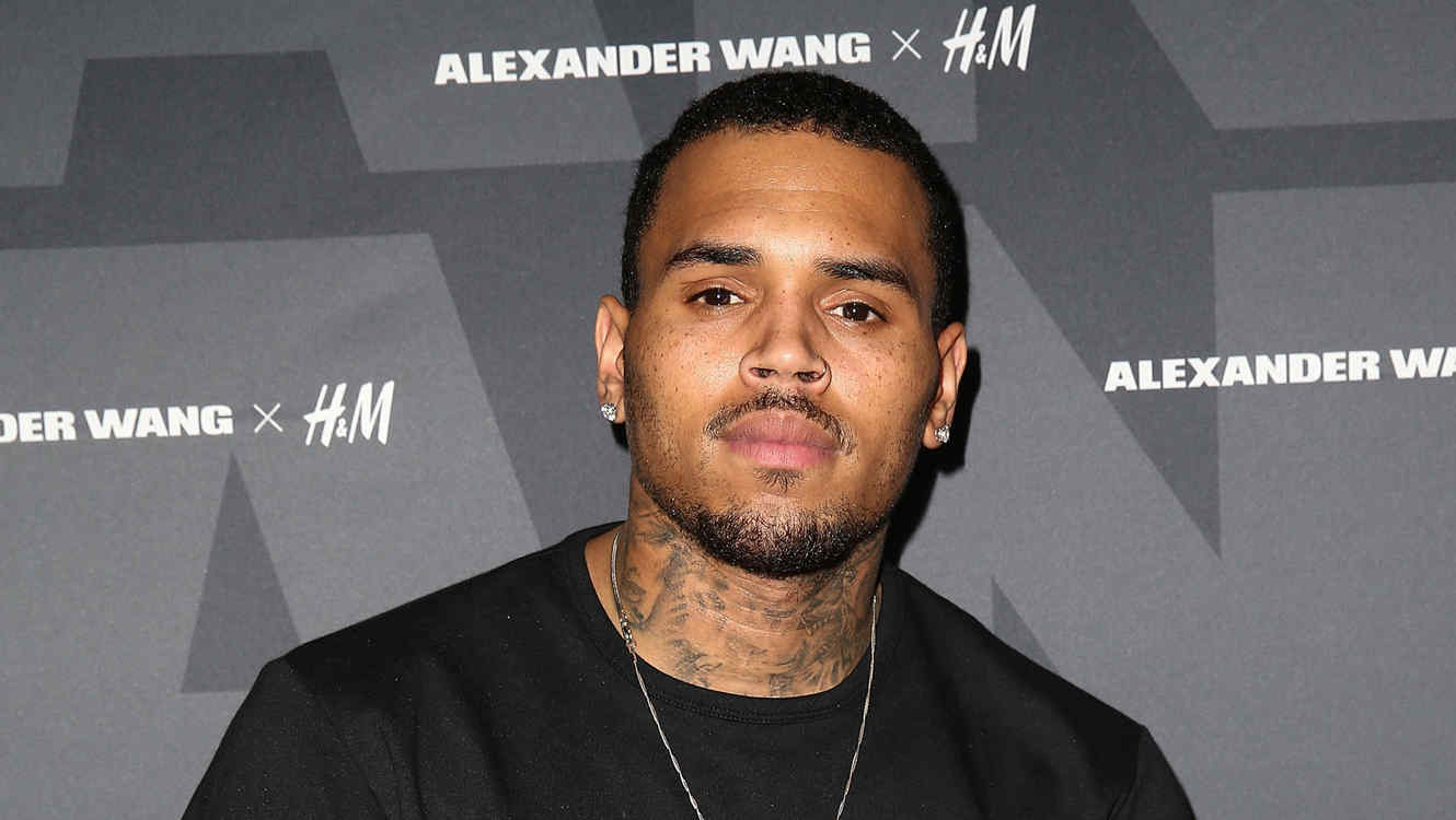 Chris Brown posando en la alfombra de Alexander Wang x H&M Pre-Shop Party