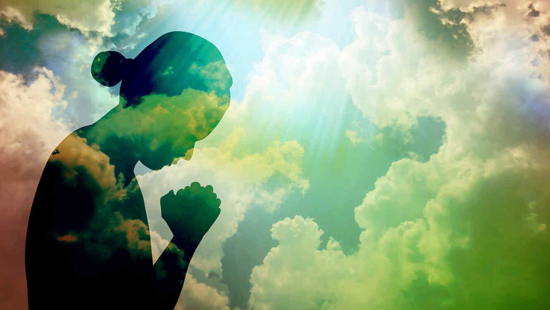 silueta de persona rezando