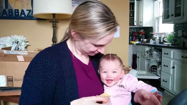 Bebé en brazos de madre riéndose