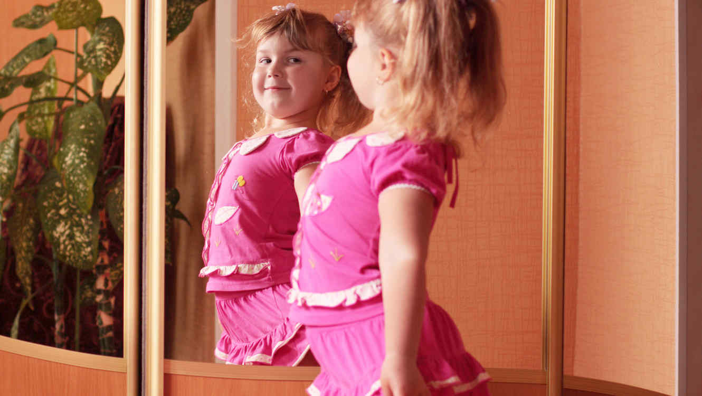 Niña vestida de rosado se mira en el espejo