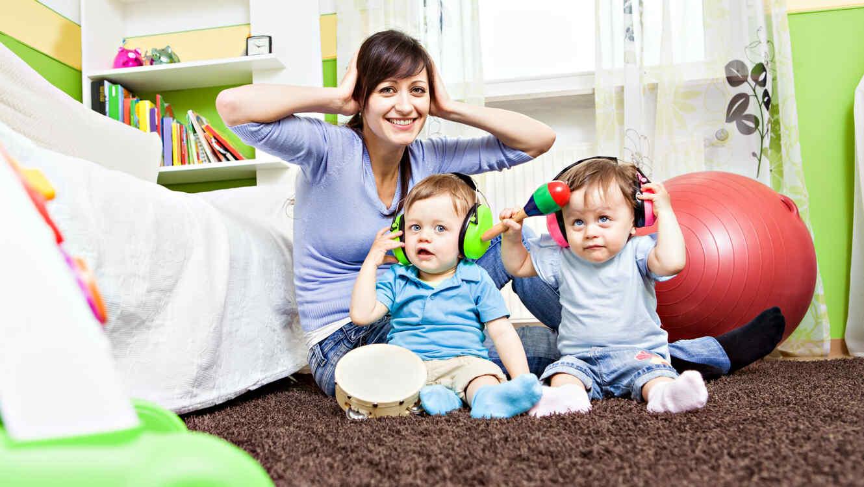 mamá con dos niños con audífonos