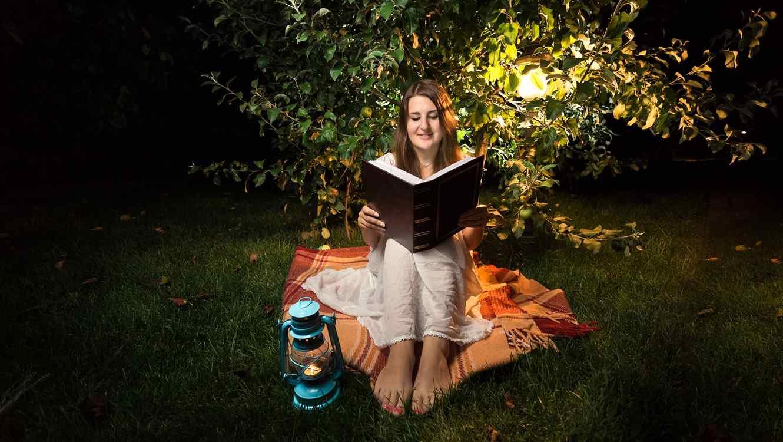 mujer descalza leyendo al aire libre de noche con farol