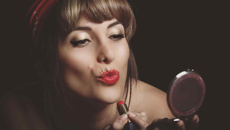 mujer pintándose los labios de rojo sosteniendo un espejito