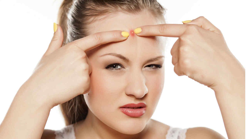 Mujer con uñas amarillas explotando un granito