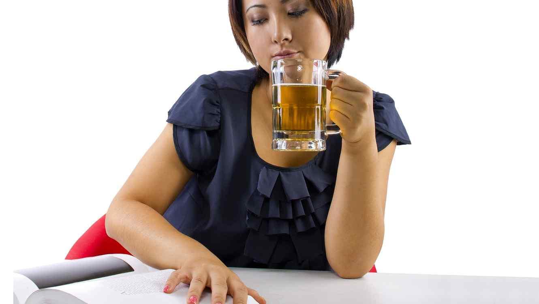 Mujer tomando cerveza y leyendo un libro