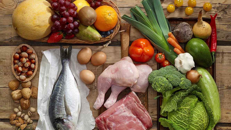 Verduras, frutas, carnes, nueces y otros alimentos saludables sobre madera