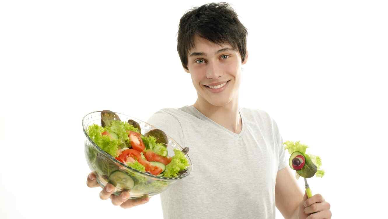 Hombre joven con camiseta blanca ofreciendo un tazón de ensalada