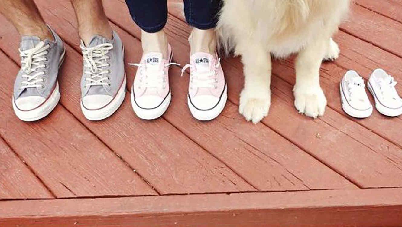 Pies de hombre, mujer y perro junto a tenis de bebé