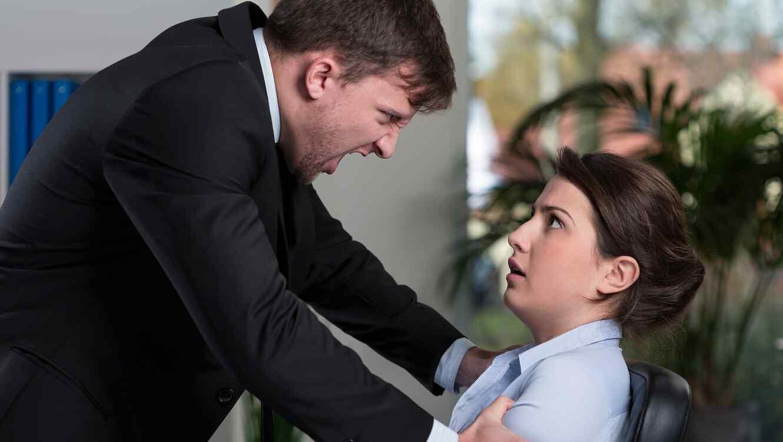 Hombre de traje furioso, gritándole a una mujer asustada