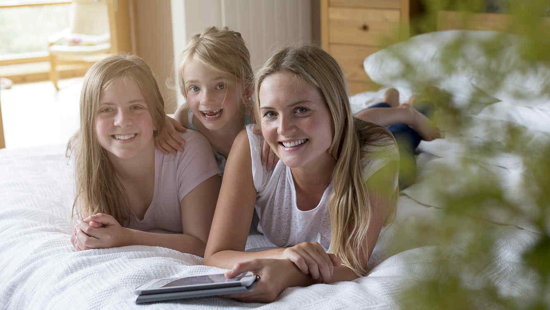 Tres hermanas rubias leyendo en la cama