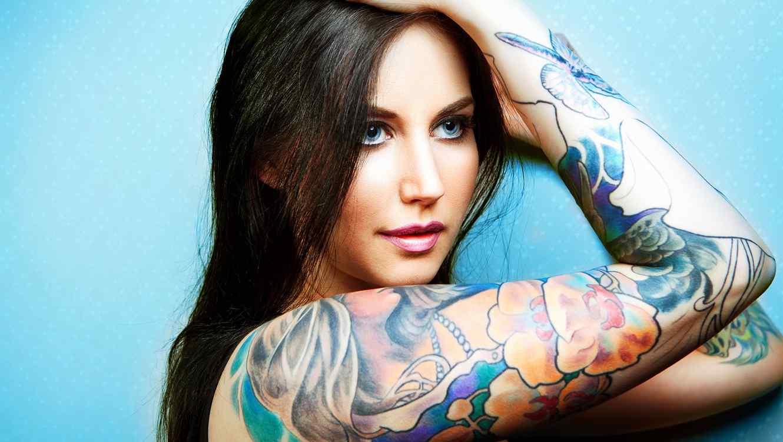 Mujer con tatuajes de colores en los brazos frente a fondo azul