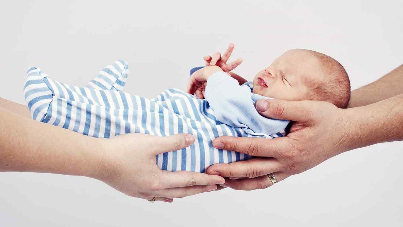 Dos personas sosteniendo al mismo tiempo a un bebé con pijama azul