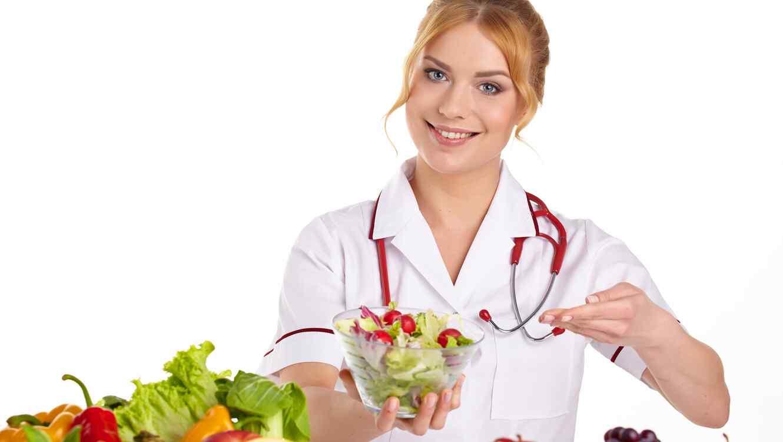 Enfermera rubia ofreciendo un tazón de ensalada