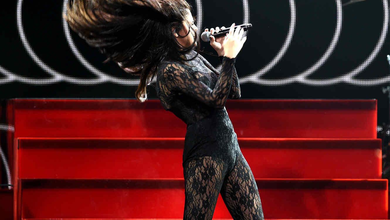 Selena Gómez cantando con el cabello al viento