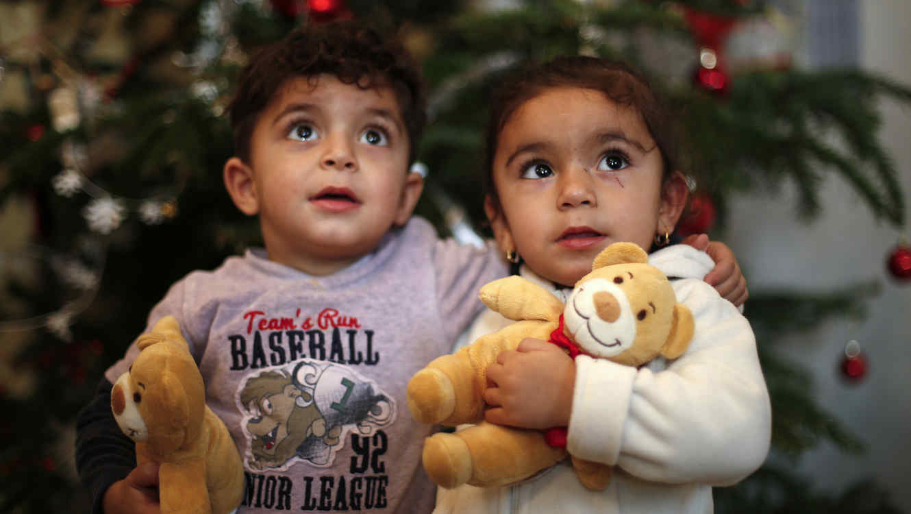 Two-year old twins Hevedar and Heve of Iraq pose in front of a Christmas tree at a refugee shelter in an evangelic church in Oberhausen