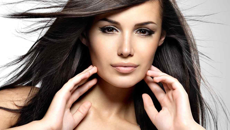 Mujer de cabello marrón oscuro con las manos junto al rostro