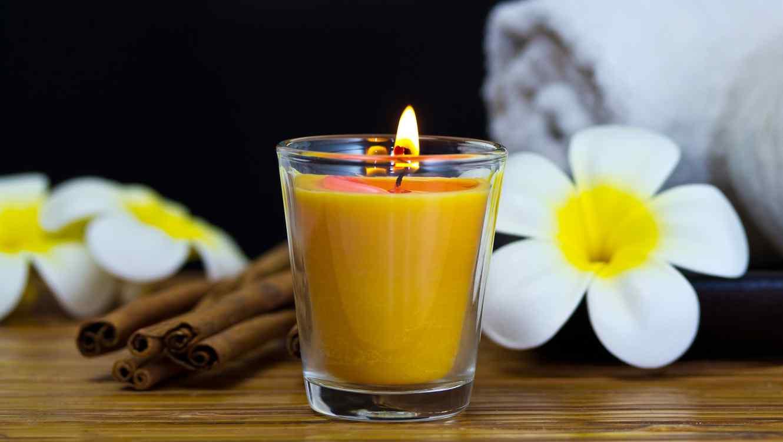 vela encendida de color amarillo al lado de flores y ramas de canela