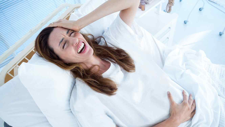 Mujer embarazada acostada en una camilla de hospital agarrándose la cabeza y la barriga