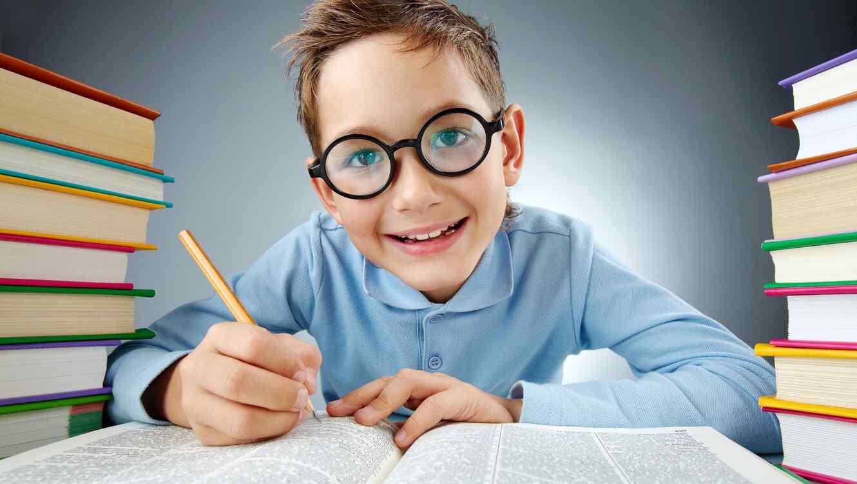 Niño con lentes escribiendo y rodeado de libros