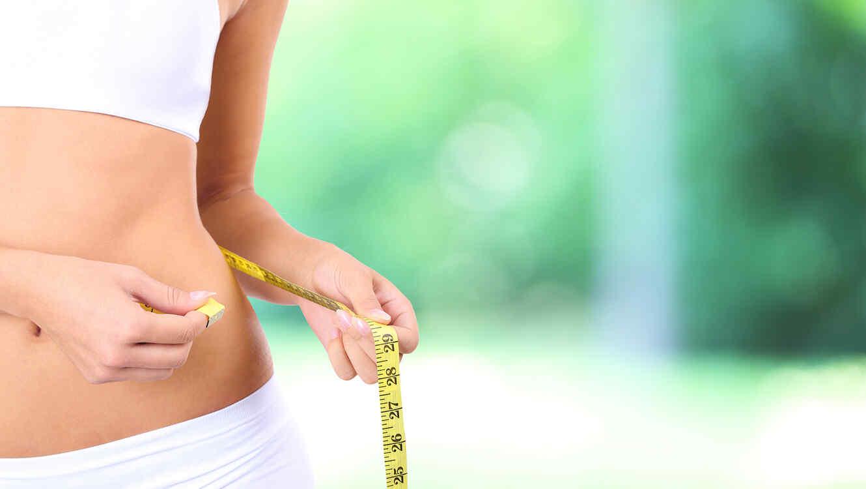 Mujer midiendo su cintura con un centímetro