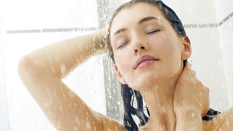Mujer de cabello marrón duchándose