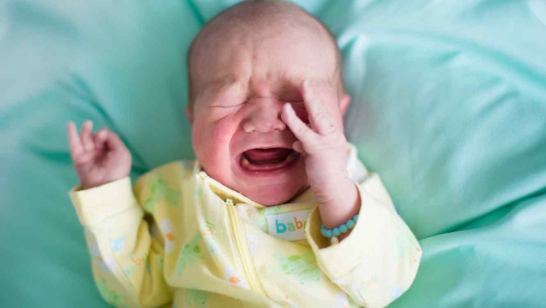 Bebé vestido de amarillo acostado sobre una sábana azul llorando