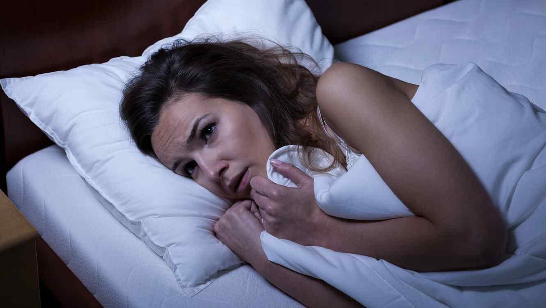 Mujer recostada en una cama tapándose con colchas blancas y con cara de asustada
