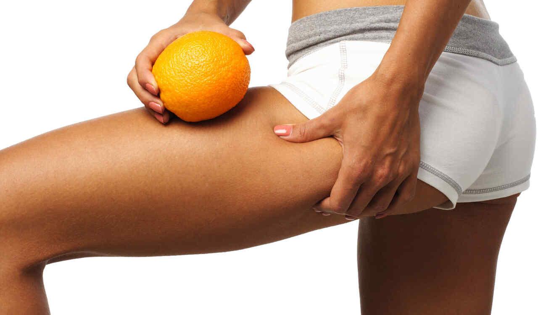 Mujer con short blanco pellizcando su pierna y sosteniendo una naranja