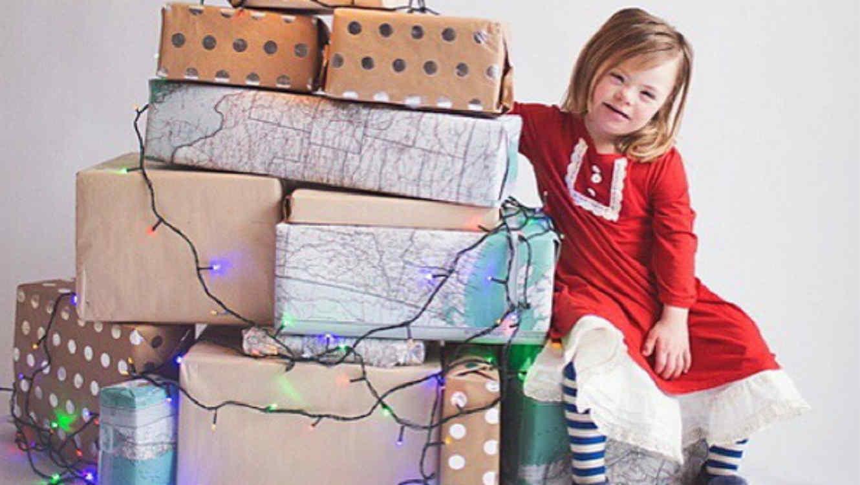 Niña con vestido rojo con regalos de Navidad