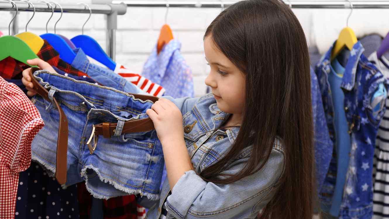 Niña en tienda de ropa viendo unos shorts de mezclilla