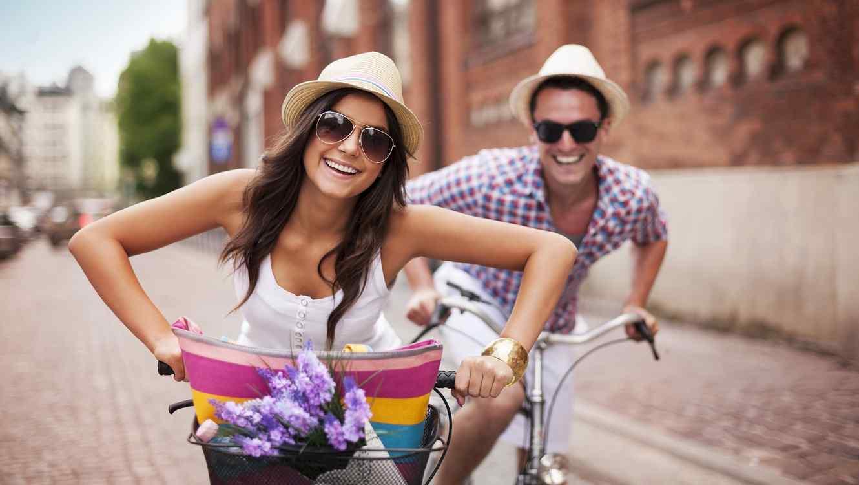 Pareja usando lentes y sombreros andando en bicicleta
