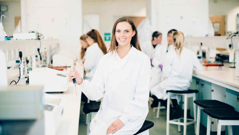 Joven estudiante sonríe en el laboratorio