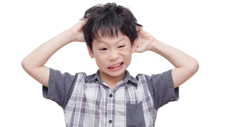 Niño rascandose la cabeza por piojos