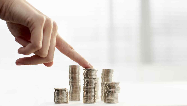 Dedo sobre monedas apiladas