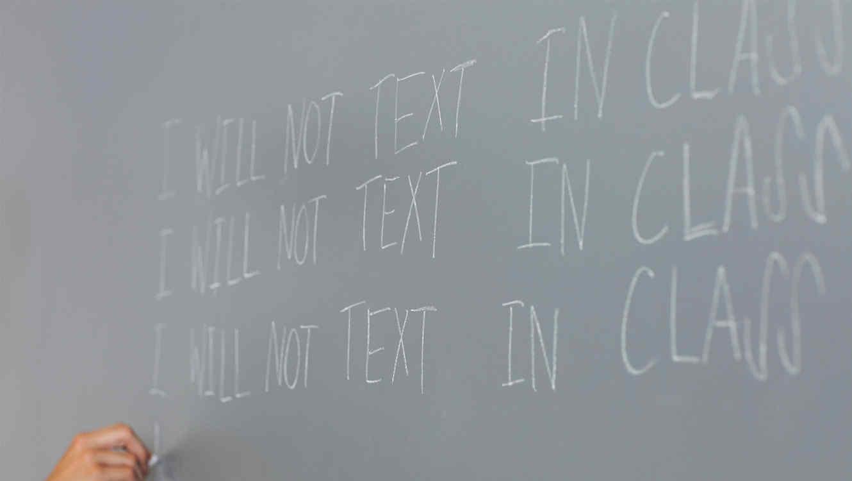 Niño escribe frases de penitencia en el pizarrón