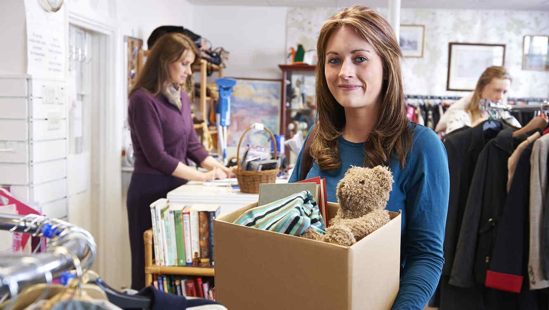 Mujer sosteniendo una caja con libros y juguetes