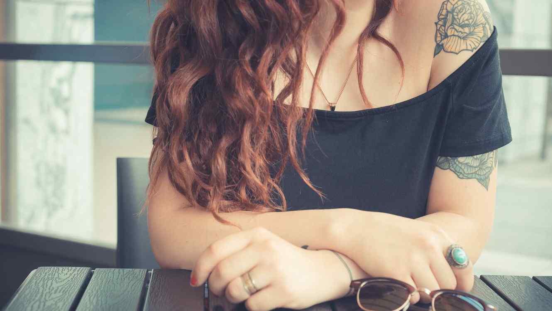 Mujer tatutada con cabello ondulado