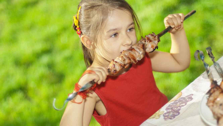 Niña con blusa roja comiendo una brocheta de carne