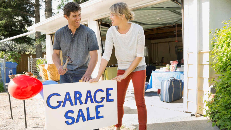 Pareja coloca cartel de venta de garaje