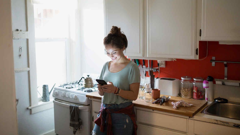 Mujer envía mensajes de texto en la cocina